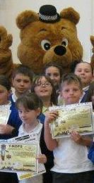PC Hug celebrates with the pupils of Ysgol Maes Glas on their ACE Detective award